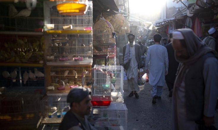 Fichier - Sur cette photo d'archives du mardi 12 octobre 2021, des Afghans traversent un marché à Kaboul, en Afghanistan. Avec le gel des avoirs afghans aux États-Unis et la réticence du monde à reconnaître les talibans, le système bancaire du pays est à l'arrêt. Les salaires impayés et la crise humanitaire qui se profile accentuent la pression sur le nouveau gouvernement taliban, qui n'a pas de solution claire. (AP Photo/Ahmad Halabisaz, File)